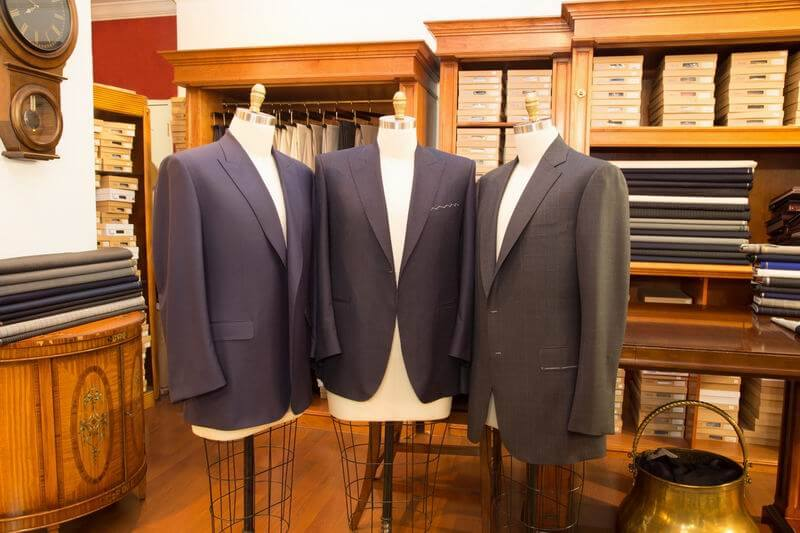 three suit jackets on stands in the Barchi Bespoke store