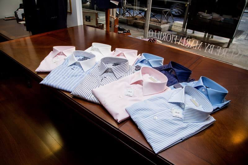 several dress shirts displayed on a wood table